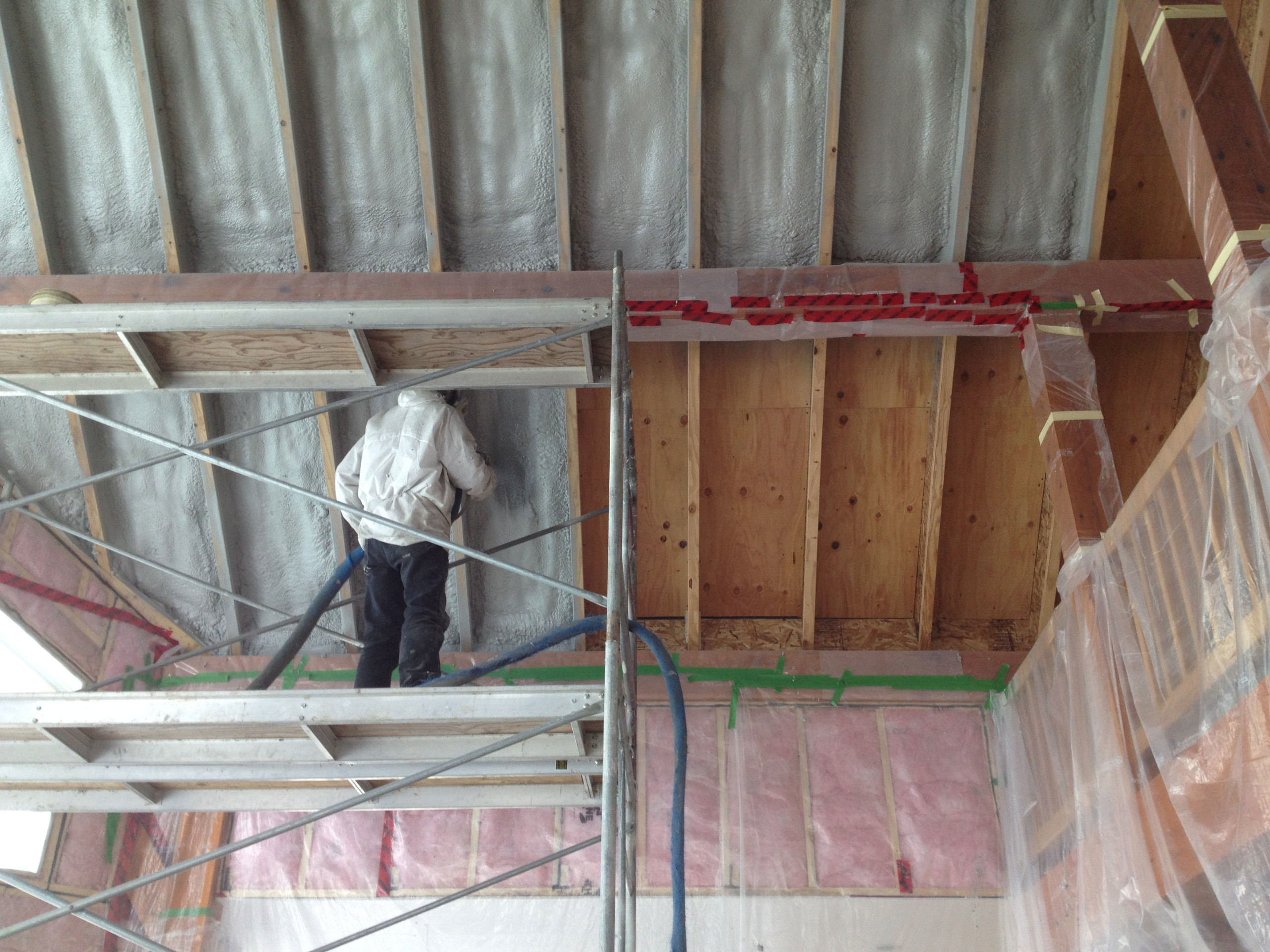 Worker spraying roof insulation